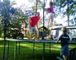 Dad and kids jumping on trampoline