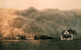 Historical photo of house surrounded by The Dust Bowl
