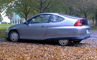 Electric car parked in log with leaves