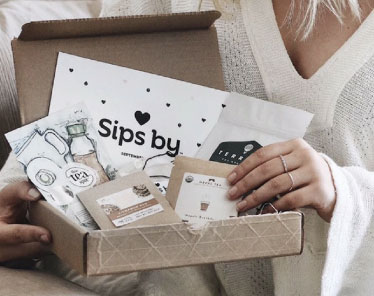 Sips by tea box in woman's hands