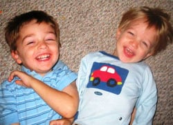Two boys on back laughing on floor